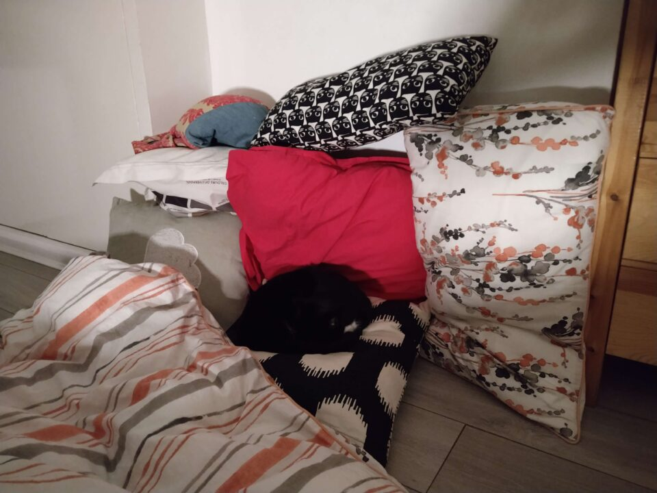 A black and white cat is curled up on a pile of colourful cushions
