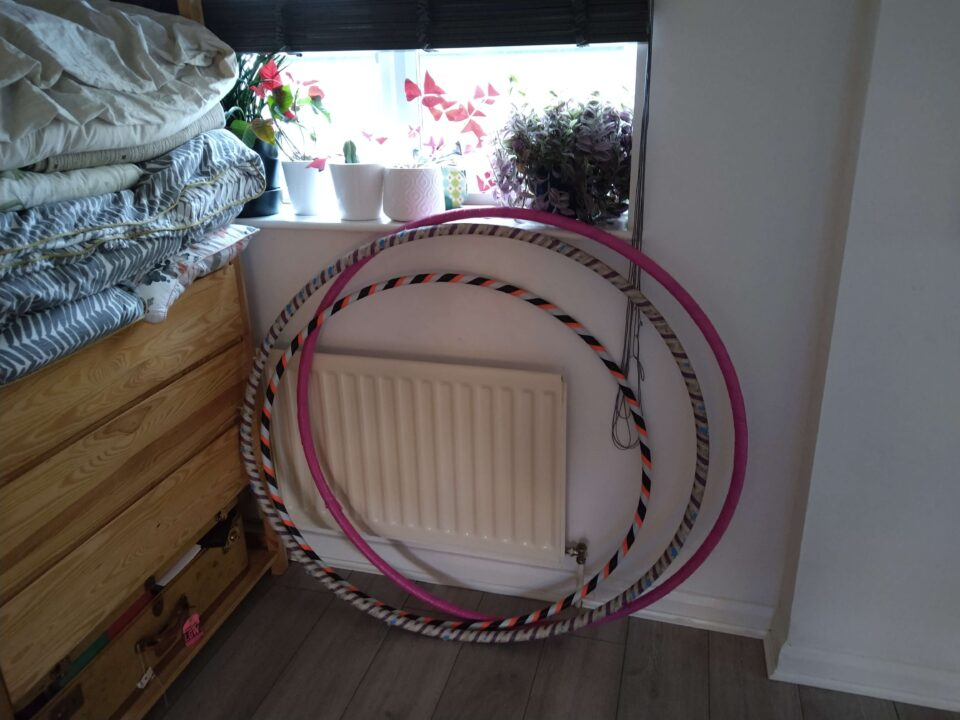 Three colourful hulahoops lean against a wall in front of a radiator and window