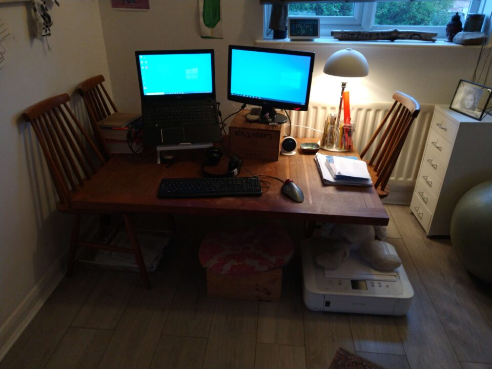 A low desk with a lit lamp and two monitors on top