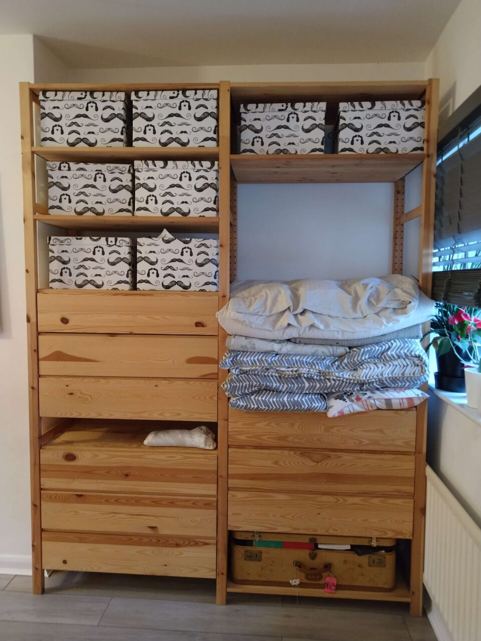 A large wooden shelving unit contains drawers, boxed and folded quilts.