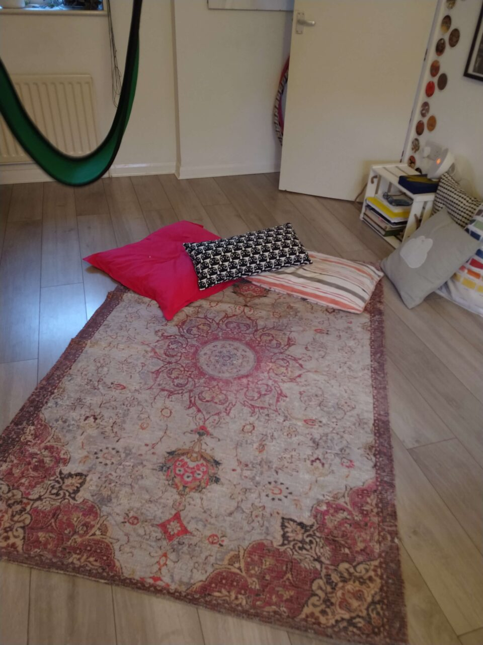 A rug is located diagonally with a small pile of cushions at one end.